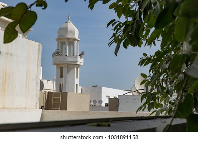 A minaret of a mosque in Bahrain is framed by some trees.