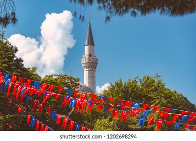 Minaret of mosque located in Istanbul, Turkey. Blue sky in background, trees and flags in foreground.