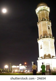 Minaret or Tower of mosque in night shot with the moon in top-left corner