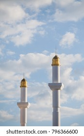 Minarets from a mosque against a cloudy sky.