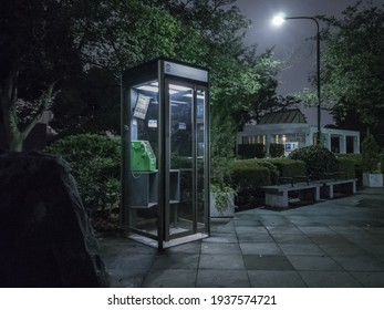 Minato City, Tokyo, JAPAN - September 13th, 2020: Urban night scene of a beautiful illuminated telephone booth in Aoyama Cemetery by night.