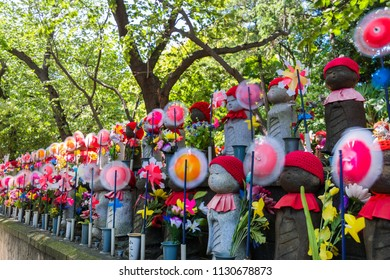 MINATO, TOKYO / JAPAN- JULY 1 2018 : One thousand Jizo of Zojoji temple. It is enshrined in hopes of the growth of children. The Jizo is covered with a red hat and the windmill is running in the wind.