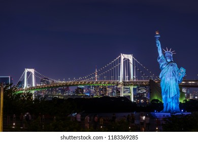 """MINATO, TOKYO / JAPAN - SEPTEMBER 5 2018 : Night view of the observation deck of """"Odaiba Beach Park"""". You can look at the lighted-up rainbow bridge. The Statue of Liberty is a symbol of Odaiba."""