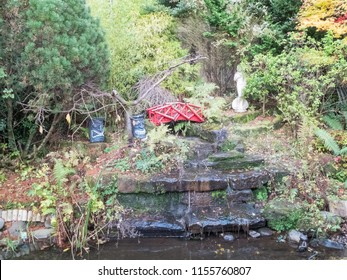 A minature garden waterfall feature with ornaments and running water.