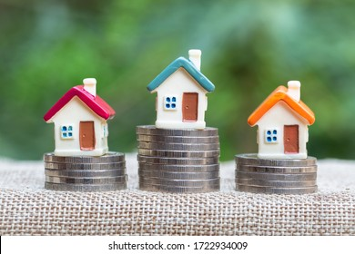 Minature houses resting on coin stacks, concept for property ladder, mortgage and real estate investment