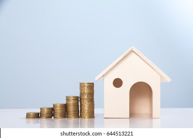 Minature houses resting and pound coin stacks concept for property ladder, mortgage and real estate investment,finance and money background concept