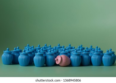 Minature jars in gender colours pink and blue;pink knocked down while crowd of blue standing around watching on green backround. Concept of sightseer, voyerism and female minority