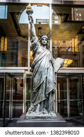 A minature Statue of Liberty outside a building in Manhattan.