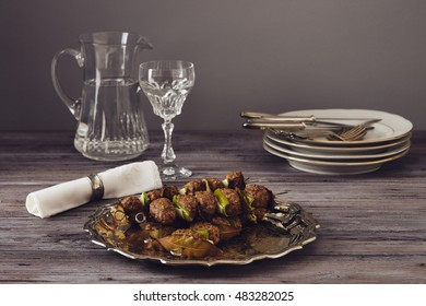 mince meatball on a spit (Italian dish) surrounded by glass, dishes and cuttlery, an elegant napkin on the table. everything on a gray wooden table with a gray background.