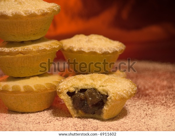 Mince pies with a dusting of icing sugar traditionally eaten at Christmas against a warm red background