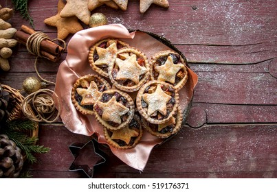 Mince pies in a vintage old plate with christmas decoration on wooden background. Traditional Christmas baking.
