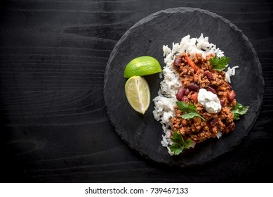 Minced lamb meat in chill sauce and rice served on dark background with blank space