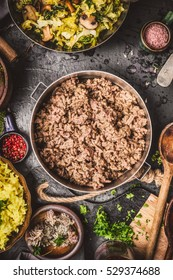 Minced Meat in cooking pot on rustic kitchen table with ingredients , rice and cooked cabbage, top view