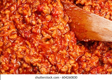 Minced meat fried in tomato sauce in the frying pan. Preparation cannelloni. Italian cuisine. Top view.