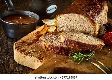Minced meat loaf on rustic wooden cutting board with spices, close-up image