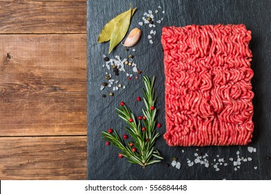 Minced meat on a slate stone black board with seasonings and fresh rosemary on wooden background, top view