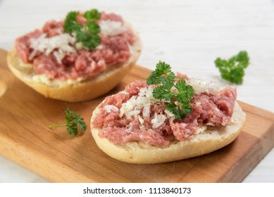 minced pork sausage, typical german mettwurst with onions and parsley garnish on a bun, kitchen board  on a white wooden table, close up with selected focus and narrow depth of field
