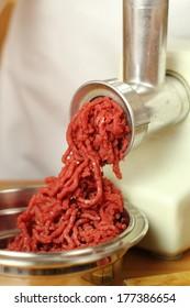 Mincing beef by meat grinder