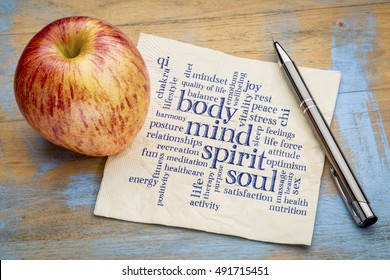 mind, body, spirit and soul concept  - word cloud on a napkin with an apple