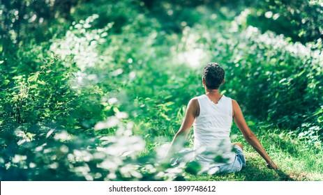 Achten Sie auf beruhigende innere Ruhe im Freien Meditation. Eine unerkennbare, bewusste Frau, die von üppiger, grüner Vegetation umgeben ist und ihre Ruhe und innere Ruhe erhöht