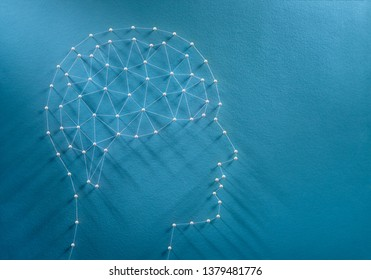 Mind concept. Network of pins and threads in the shape of a brain inside a human head symbolising consciousness.