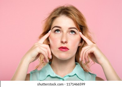 mind games telepathy thought transfer and brain power. beautiful girl concentrating on invisible object above her. index fingers on temples. young beautiful blond woman portrait on pink background.