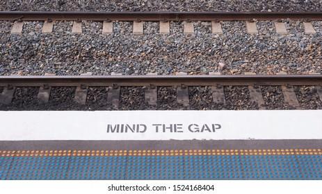 """MIND THE GAP"" sign on train platform's floor"