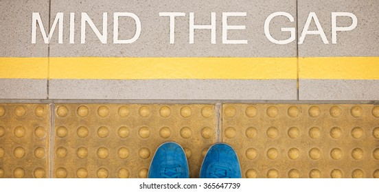 Mind the gap sign painted on train station's platform edge, top view with man's feet or shoes