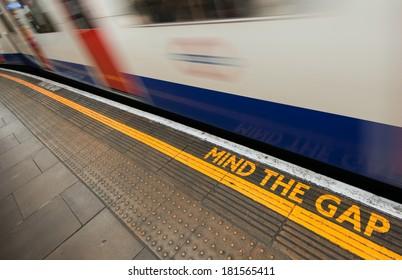 Mind the gap sign with speeding train in London underground.
