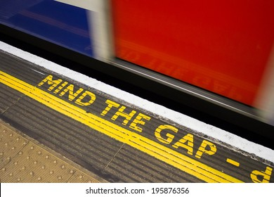 Mind the gap sign with a train moving by it at speed
