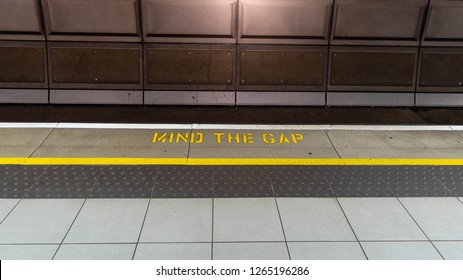 Mind the gap typical sign painted on a tube platform edge. Painted warning on the floor. Mind the gap sign painted on train station's platform edge, top view.  Rail way user caution concept.