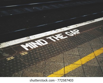 A Mind the Gap warning painted on the edge of the platform of a train station