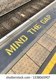 Pensez au panneau d'avertissement de l'écart au bord d'une plate-forme ferroviaire britannique.