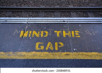 Mind the Gap warning sign painted in yellow at the edge of train platform - UK