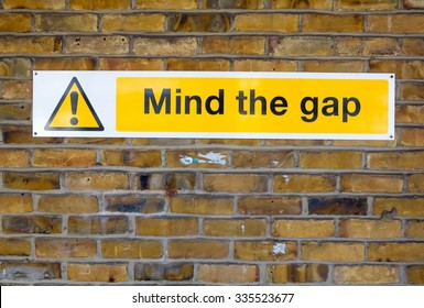 'Mind the Gap' yellow warning sign from the London Underground on a brick wall background