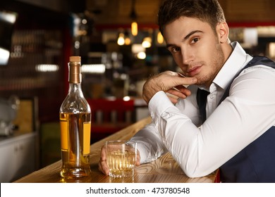 Mind if I join? Shot of an attractive young man looking to the camera seductively sitting at the bar having a glass of whiskey