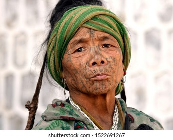 """MINDAT, CHIN STATE / MYANMAR - MARCH 21, 2019: Old Chin Muun tribal woman (""""spider woman"""") with traditional facial tattoo poses for the camera, on March 21, 2019."""