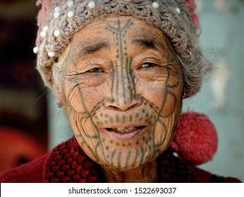 """MINDAT, CHIN STATE / MYANMAR - MARCH 21, 2019: Elderly Chin Muun tribal woman (""""spider woman"""") with traditional facial tattoo poses for the camera, on March 21, 2019."""