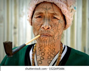 """MINDAT, CHIN STATE / MYANMAR - MARCH 21, 2019: Elderly Chin Muun tribal woman (""""spider woman"""") with traditional facial tattoo smokes a pipe with local tobacco, on March 21, 2019."""