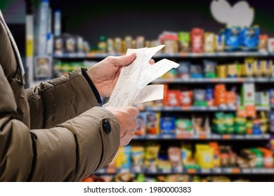 Minded man viewing receipts in supermarket and tracking prices