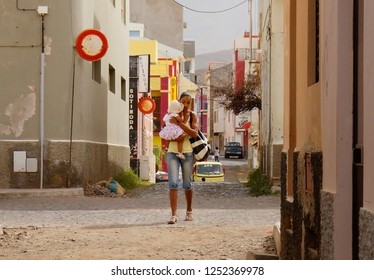 Mindelo, Cape Verde, Africa, 12/07/2012, city residents. Mindelo is the second largest city in Cape Verde. The young woman with a baby is walking around the city.
