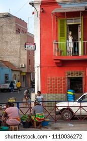 MINDELO, CAPE VERDE - DECEMBER 07, 2015: Life in Mindelo, residents selling goods at the square market fair. Red wall with a mannequin in the window
