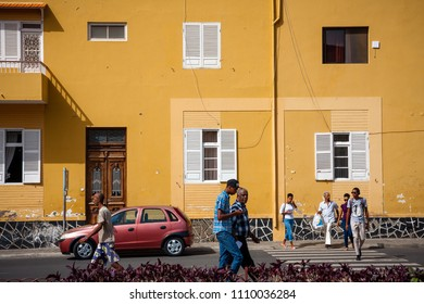 MINDELO, CAPE VERDE - DECEMBER 07, 2015: Life in Mindelo, residents walking the streets. Town architecture,  large yellow building wall. Africa