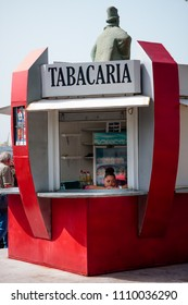 MINDELO, CAPE VERDE - DECEMBER 07, 2015: Tabacaria - tobacco shop hut selling drinks. Woman in the window thinking and dreaming