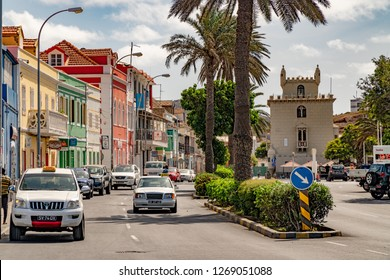 MINDELO, CAPE VERDE - OCTOBER 28, 2018: cars driving along Avenida Marginal in downtown Mindelo, Cape Verde with Torre de Belem in the background on October 28, 2018.