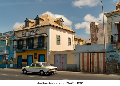 MINDELO, CAPE VERDE - OCTOBER 28, 2018: Taxi passing by historic buildings in the center of Mindelo, Cape Verde.