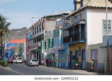 MINDELO, CAPE VERDE - OCTOBER 28, 2018: people walking in frnt of historic houses along Avenida Marginal in Mindelo, Cape Verde on October 28, 2018.