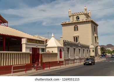 MINDELO, CAPE VERDE - OCTOBER 28, 2018: car passing by the historic building hosting the fish market with Torre de Belém in the background.