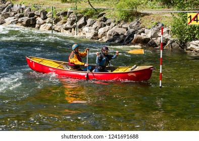 MINDEN, ONTARIO - SEPTEMBER 8, 2018: Mixed team in a tandem whitewater slalom canoe at Gull River in Minden, Ontario, Canada.