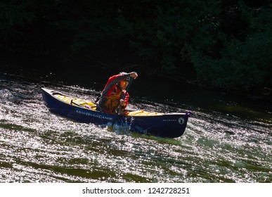 MINDEN, ONTARIO - SEPTEMBER 8, 2018: An unidentified paddler steers a whitewater canoe down the Gull River in Minden, Ontario, Canada.